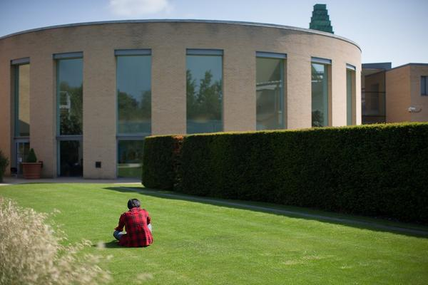 Person sitting on grass outside the back of Said Business School